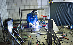 Mitarbeiter in Blaumann der Trockeneisstrahlgerät schweißt