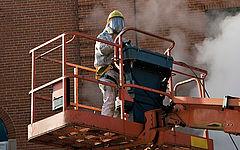 Mann in weißem Schutzanzug bei der Nutzung einer Trockeneisstrahlmaschine auf einem Kran